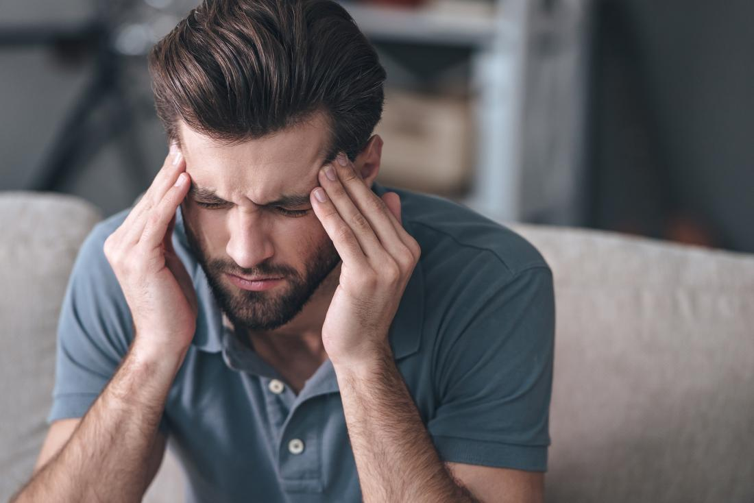 man-with-migraine-headache-massaging-his-temples-and-frowning
